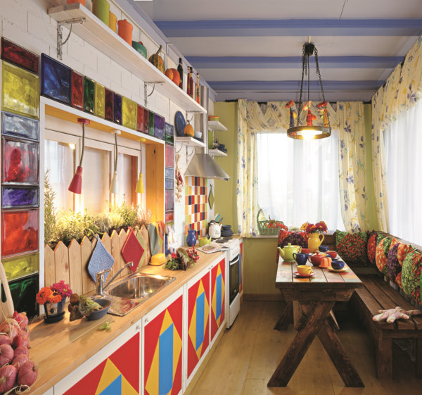 1-veranda-cozy-country-house-porch-kitchen-wooden-ceiling-beams-in-Mediterranean-style-bright-multicolored-interior-cabinets-red-yellow-blue-green-glass-blocks-geometrical-patterns-dining-table-bench-lamp-open-racks-window