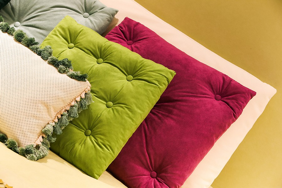 2-2-new-show-room-concept-store-in-Milan-Italy-2017-Alcantara-material-collection-in-interior-design-bedroom-pale-yellow-upholstered-bed-multicolor-capitone-throw-pillows-decorative-green-fuchsia-gray-white