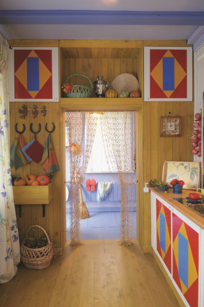 3-veranda-cozy-country-house-porch-kitchen-wooden-walls-ceiling-beams-in-Mediterranean-style-bright-multicolored-interior-cabinets-red-yellow-blue-geometrical-pattern-floor-basket-still-life-blue-floor