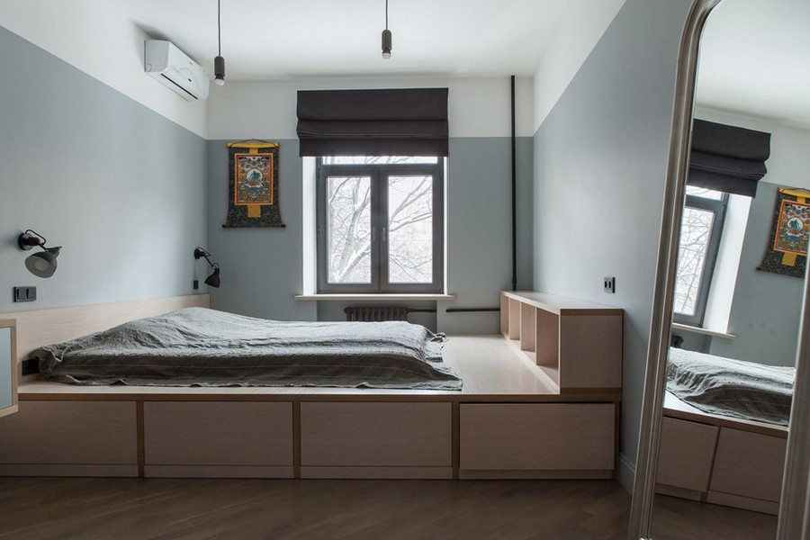 5-1-bachelor's-pad-interior-design-loft-style-brutal-bedroom-light-wooden-poidum-with-storage-drawers-mattress-book-shelves-big-full-length-mirror-gray-walls-black-roman-blinds