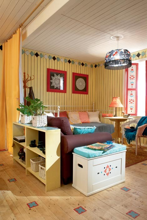 0-country-style-living-room-lounge-interior-design-summer-house-yellow-wooden-planks-walls-curtains-room-divider-stenciled-painted-furniture-chest-sofa-bed-retro-lamp-shelves-bright-patterns-rustic-ornaments