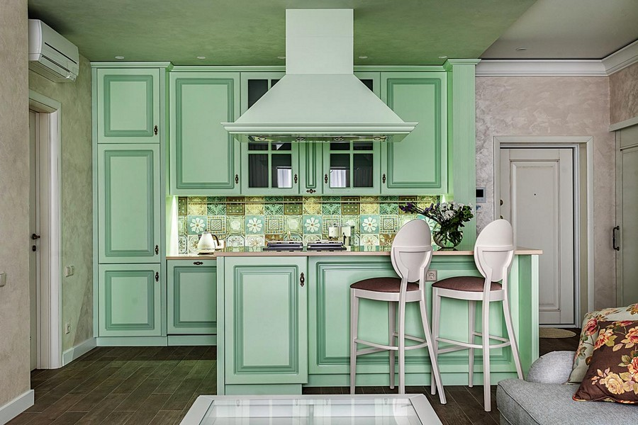 0-pale-mint-green-kitchen-interior-design-in-Mediterranean-style-island-soild-wood-cabinets-traditional-beige-worktop-cooker-hood-extractor-bar-stools-cheerful-backsplash-square-tiles-LED-light-open-concept