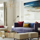 1-2-modern-neo-classical-style-interior-design-living-room-bay-window-beige-walls-artwork-painting-blue-sofa-red-accents-couch-pillows-round-metal-coffee-table-brass-lamp-padded-stools-arm-chairs-floor-lamps-rug