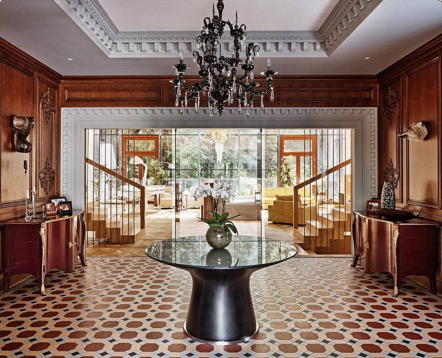 1-Engish-style-big-hall-hallway-interior-design-floor-tiles-oak-wood-wall-panels-dark-brown-furniture-console-tables-symemtrical-arrangement-round-table-chandelier-cement-concrete-cornices