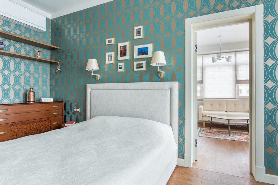 2-1-modern-bedroom-interior-design-greenish-blue-geometrical-wallpaper-Indulgence-collection-by-Harlequin-white-upholstered-bed-style-of-1950s-wooden-chest-of-drawers-open-racks-bookshelves-art-wall