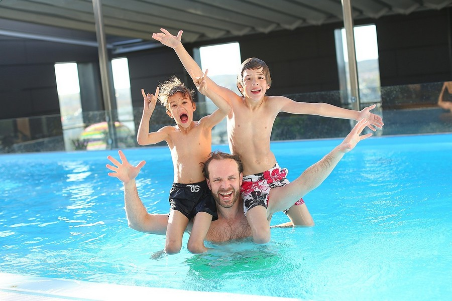 2-Father-and-kids-sons-boys-have-fun-in-outdoor-swimming-pool-sitting-on-the-shoulders-dad