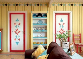 2-country-style-living-room-lounge-interior-design-summer-house-yellow-wooden-planks-walls-stenciled-painted-furniture-doors-chest-of-drawers-bright-patterns-rustic-ornaments-cupboard-red-blue-accents