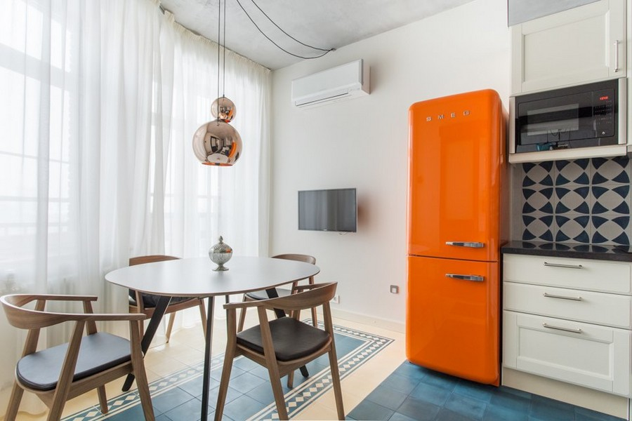 3-0-eclectic-style-modern-of-1950s-kitchen-interior-design-blue-and-white-concrete-wall-tiles-backsplash-geometrical-pattern-black-countertop-white-cabinets-orange-retro-Smeg-refrigerator-round-dining-table