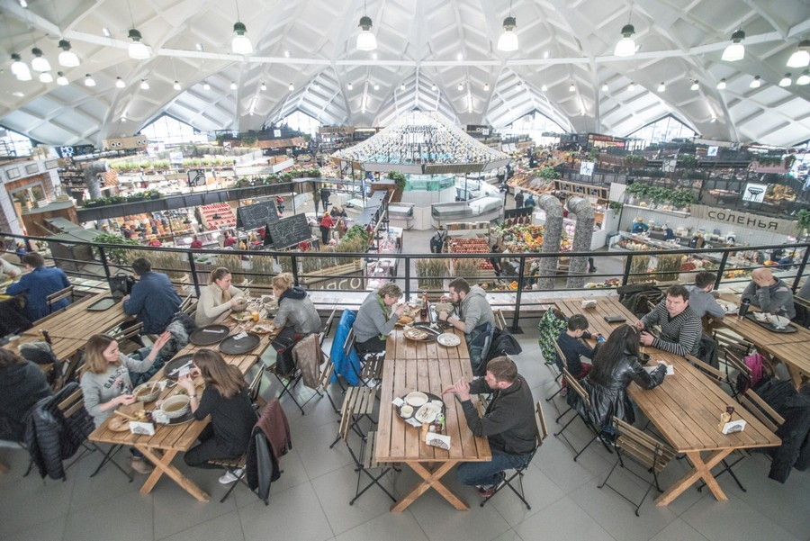3-2-cozy-beautiful-courtyard-style-covered-food-market-interior-design-Danilovsky-market-in-Moscow-cafes-mezzanine-floor-top-food-court-wooden-dining-tables-benches
