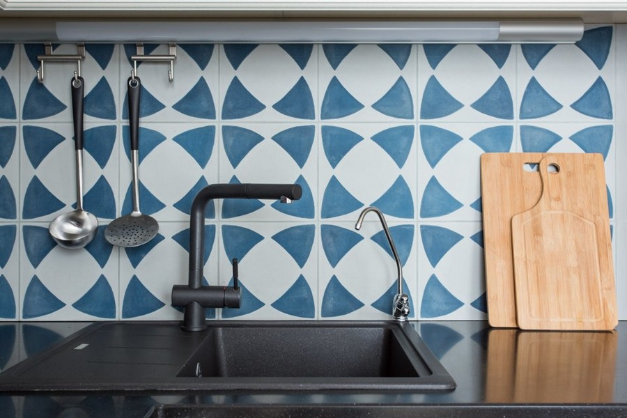 3-2-kitchen-blue-and-white-concrete-wall-tiles-backsplash-geometrical-pattern-black-countertop-worktop-faucet-sink-wooden-cutting-board
