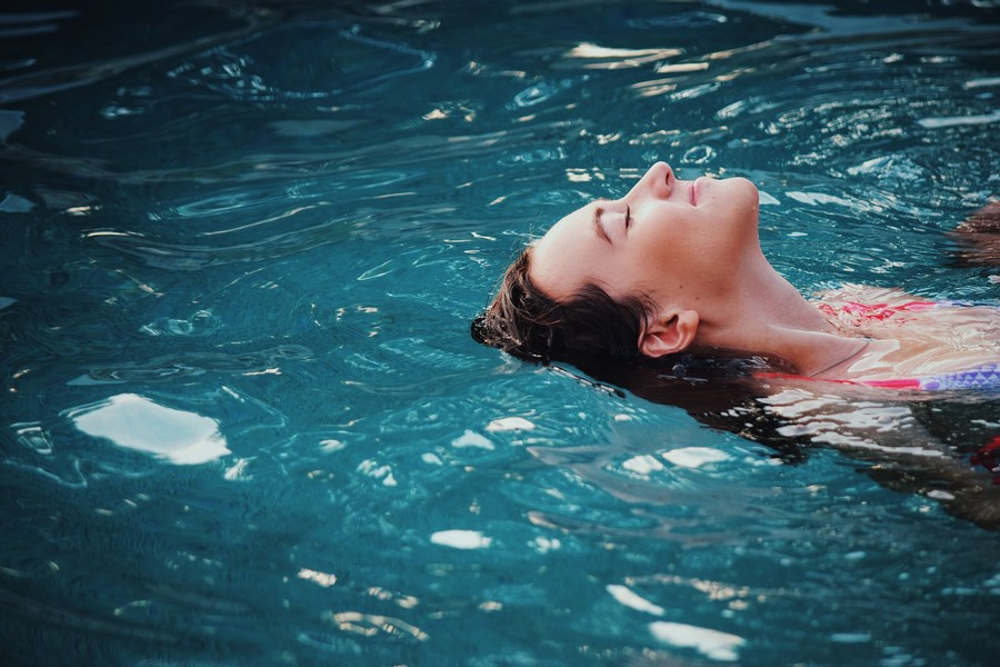 3-beautiful-woman-lying-on-her-back-in-a-swimming-pool