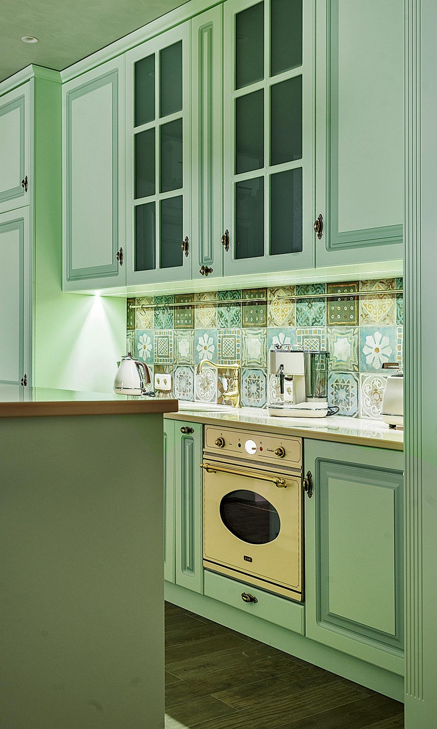 3-pale-mint-green-kitchen-interior-design-in-Mediterranean-style-island-soild-wood-cabinets-beige-worktop-cooker-hood-glass-cabinets-stove-brass-faucet-handles-rails-cheerful-square-tiles-backsplash-kettle
