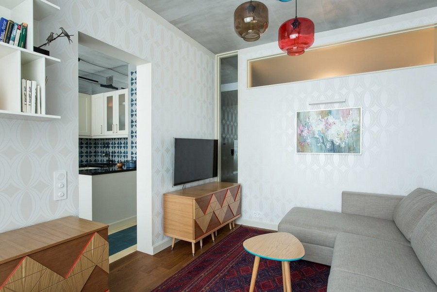4-2-eclectic-living-room-interior-design-in-style-of-1950s-multicolor-pendant-lamps-white-wallpaper-indulgence-collection-by-harlequin-gray-sofa-wooden-coffee-table-concrete-ceiling-transom-geometrical-console
