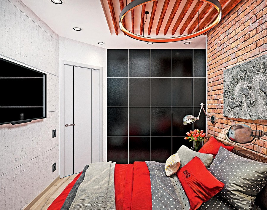 4-2-industrial-loft-style-bright-interior-design-with-red-and-yellow-accents-windowless-bedroom-faux-brick-wall-TV-set-black-built-in-closet-ring-lamp-wooden-planks-ceiling-decor-angled-wall-door-bed-spot-lights-roo