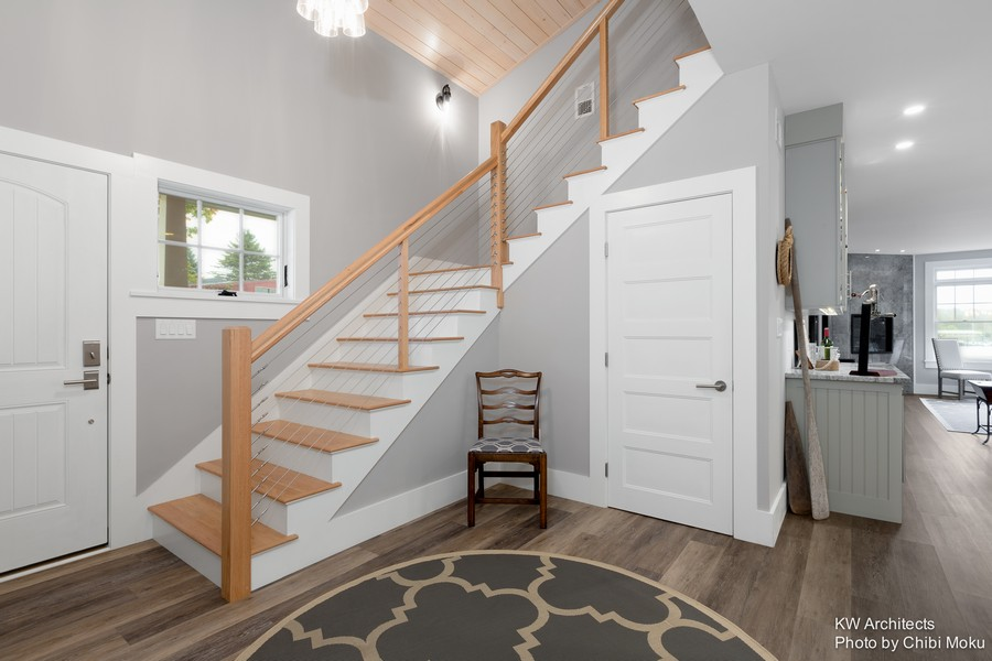 4-contemporary-style-interior-design-entry-entrance-hall-hallway-gray-walls-wire-metal-tension-stair-rails-wooden-planks-ceiling-nickel-gap-whietwashed-white-doors-round-circular-rug