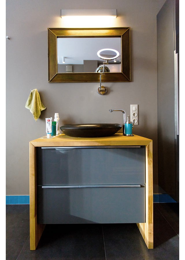 6-1-vanity-unit-by-IKEA-gray-painted-wash-basin-cabinet-drawers-re-made-with-wooden-countertop-black-top-mounted-natural-basalt-sink-drop-shaped-rectangular-mirror-with-light-lamp-azure-blue-tiles-soap-dispenser-gray-walls