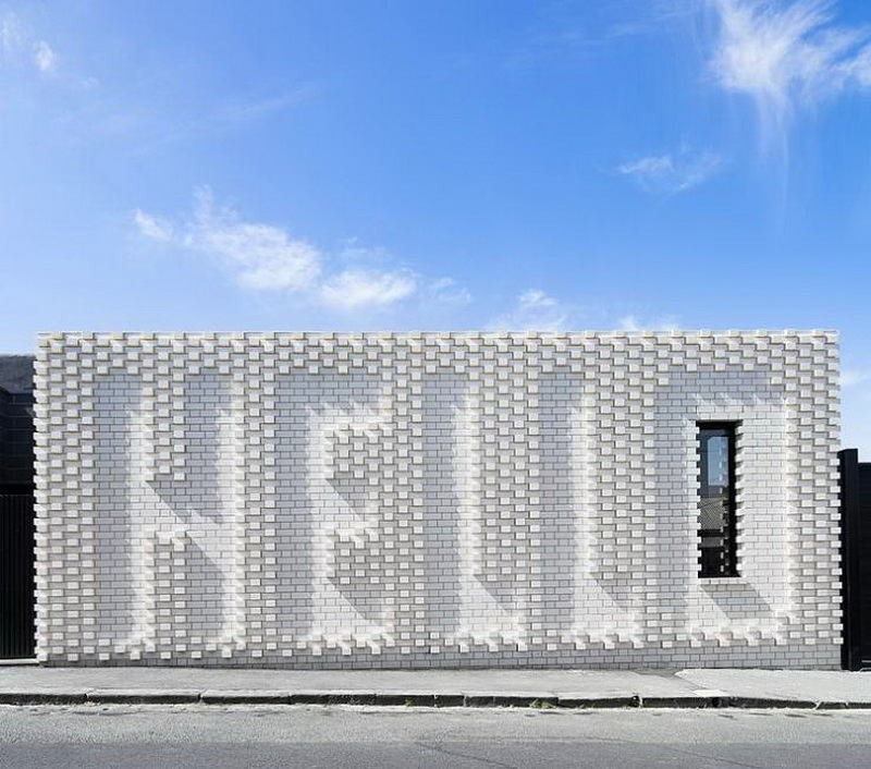 1-creative-small-house-in-Melbourne-suburbs-Australia-white-brick-exterior-wall-with-hello-word-narrow-tall-window