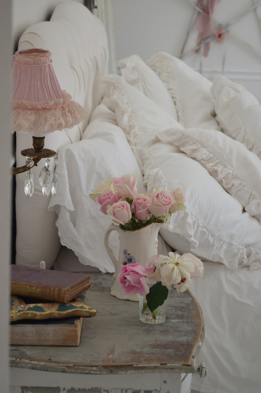 1-shabby-chic-style-interior-design-bedroom-white-pillows-laces-pale-pink-table-lamp-romantic-aged-wooden-bedside-table-nightstand-roses-jug-crystal-pendants-glass
