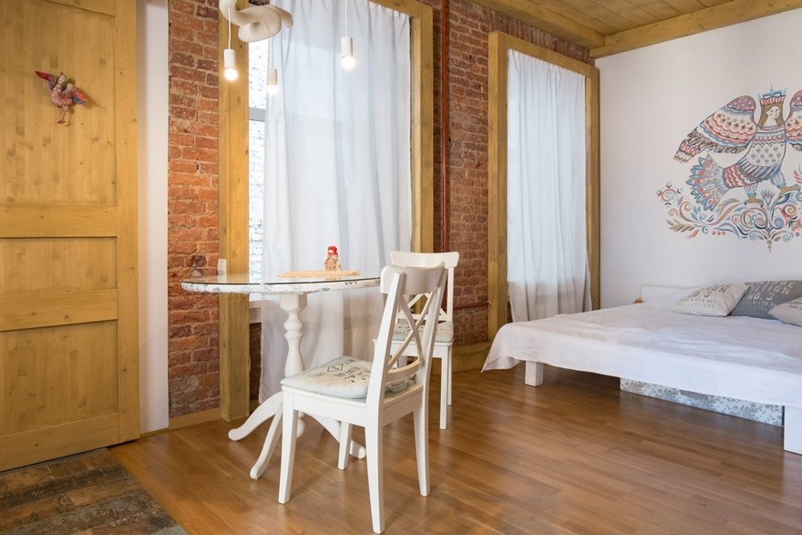 1-studio-apartment-interior-design-with-historical-brick-wall-masonry-white-wall-folk-motifs-Gamayun-mythical-paradise-bird-painting-white-wooden-bed-dining-table-wooden-ceiling-two-windows