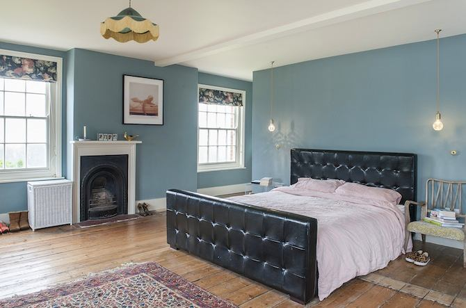 14-old-country-house-interior-design-vintage-style-bedroom-black-leather-upholstered-bed-eclectic-fireplace-blue-walls-lamp-chair-bulbs-roman-blinds