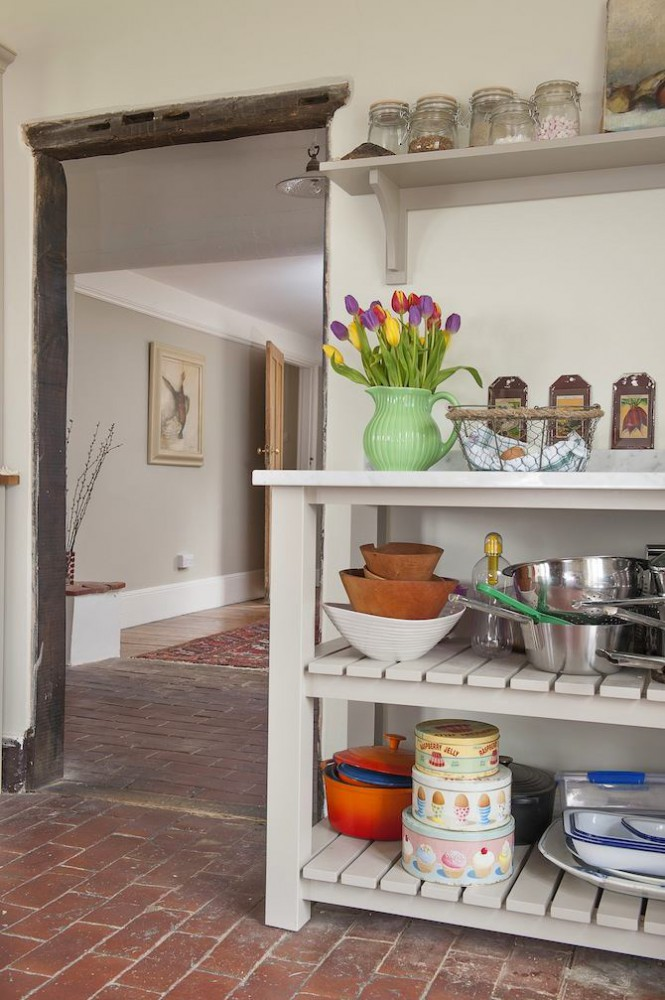 15-1-old-country-house-interior-design-vintage-style-kitchen-open-racks-red-brick-floor-masonry-wooden-shelving-unit-shelves-tulips-jug-cookware-jars