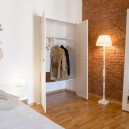 3-studio-apartment-interior-design-folk-style-ethnicak-motifs-white-wall-painting-mythical-bird-masonry-historical-brick-wall-hand-made-bed-built-in-wardrobe-closet-floor-lamp-full-length-mirror
