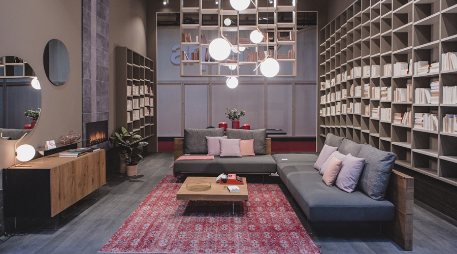 4-1-Lago-Italian-furniture-for-famous-women-Chiara-Gamberale-contemporary-style-living-room-interior-design-wall-to-wall-bookshelves-home-library-gray-corner-sofa-with-glass-base-legs-coffee-table-fireplace