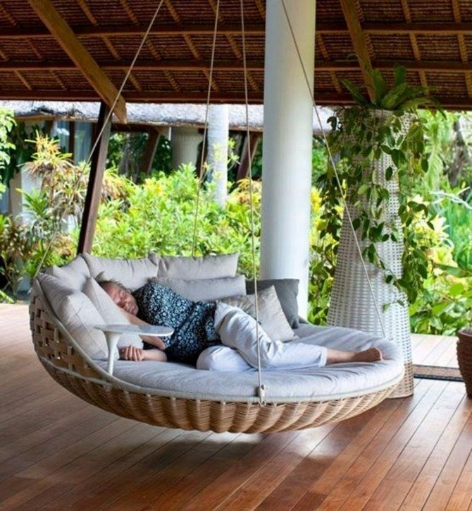 4-1-beautiful-garden-swing-suspended-floating-bed-wicker-gray-cushions-man-sleeping-on-a-terrace-outdoor
