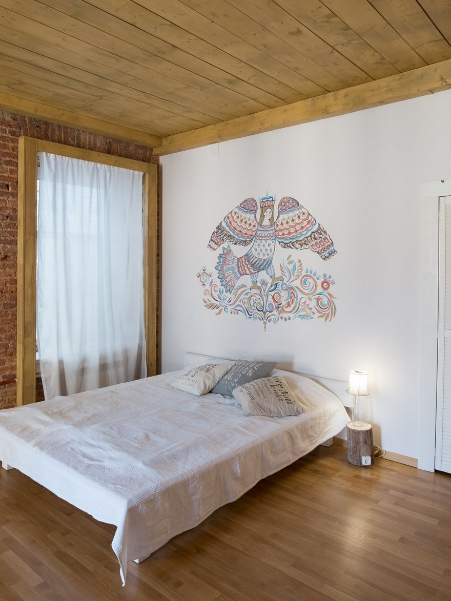 4-studio-apartment-interior-design-with-historical-brick-wall-masonry-white-wall-folk-motifs-Gamayun-mythical-paradise-bird-painting-white-wooden-bed-wooden-ceiling-window-sheer-curtains