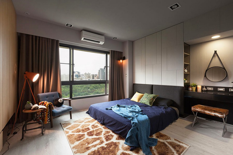 5-1-bedroom-interior-design-Taiwan-laconic-light-walls-dressing-table-black-headboard-brown-curtains-blue-bedspread-cover-armc-chair-floor-lamp-rug-panoramic-windows