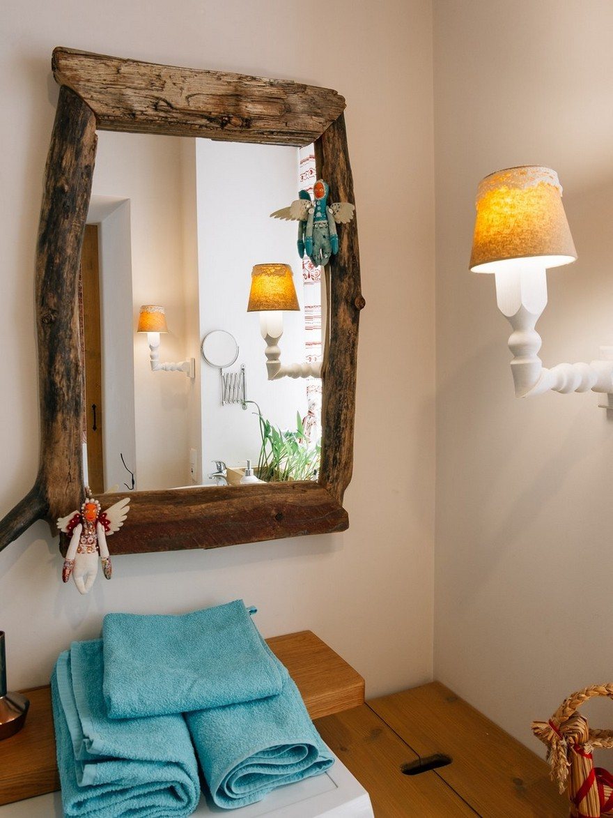 5-2-bathroom-interior-design-white-walls-wall-lamps-sconces-blue-towels-wooden-mirror-decor-rustic-folk-style-wooden-racks-shelves