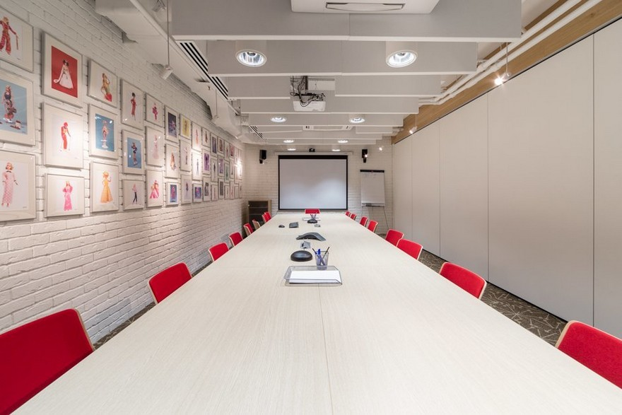 5-3-Mattel-office-interior-design-Russia-Moscow-toys-seller-meeting-room-narrow-long-elongated-space-white-faux-brick-walls-Barbie-wall-art-pictures-pink-chairs-exposed-ceiling-wires-projector-screen