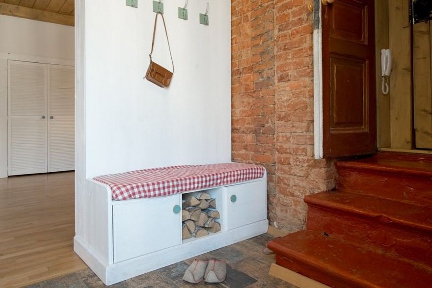 6-3-entry-hallway-entrance-hall-interior-design-in-studio-apartment-white-shoe-bench-coat-racks-folk-motifs-historical-brick-wall-masonry-stairs-wooden-door-checquered-fabric-cushion-firewood-log-fire-oven-style