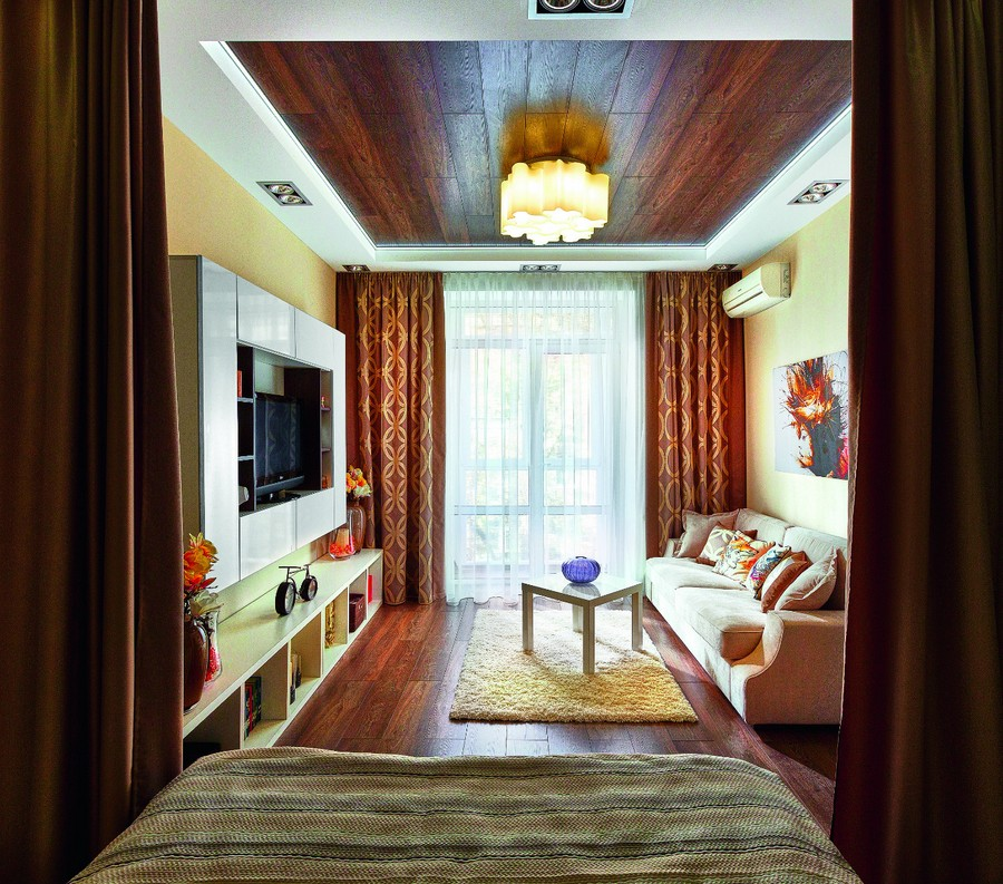 9-wooden-ceiling-decor-in-interior-design-dark-brown-laminate-floor-living-room-yellow-walls-elongated-room-sofa-coffee-table-TV-set-shelving-unit-around-TV-air-conditioner-chandelier