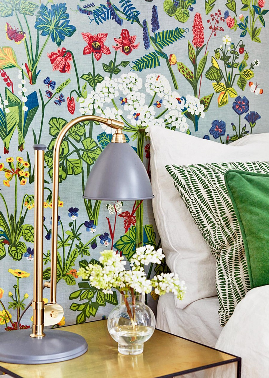 0-beautiful-wallpaper-wall-mural-wall-covering-Aurora-by-Boras-Tapeter-bedroom-accent-wall-spring-motifs-blue-background-red-white-yellow-flowers-nightstand-table-lamp-brass-decor-vase-green-pillows