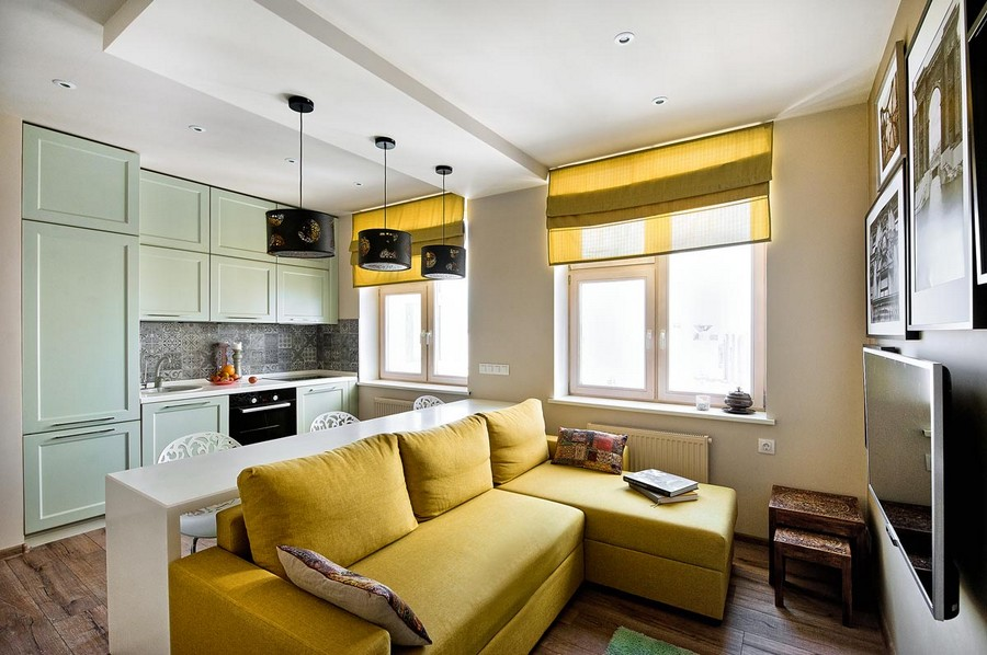 1-3-studio-apartment-interior-design-ideas-open-concept-kitchen-living-room-lounge-yellow-corner-sofa-light-green-kitchen-cabinets-pendant-lamps-TV-set-roman-blinds-Mettlach-tiles-backsplash