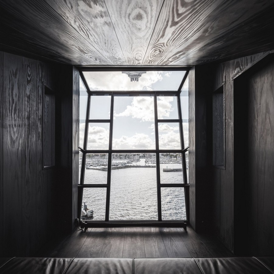 1-4-remade-reconstructed-ex-harbor-crane-apartment-in-Copenhagen-dark-black-graphite-gray-interior-corridor-leather-couch-sea-port-view-panoramic-window