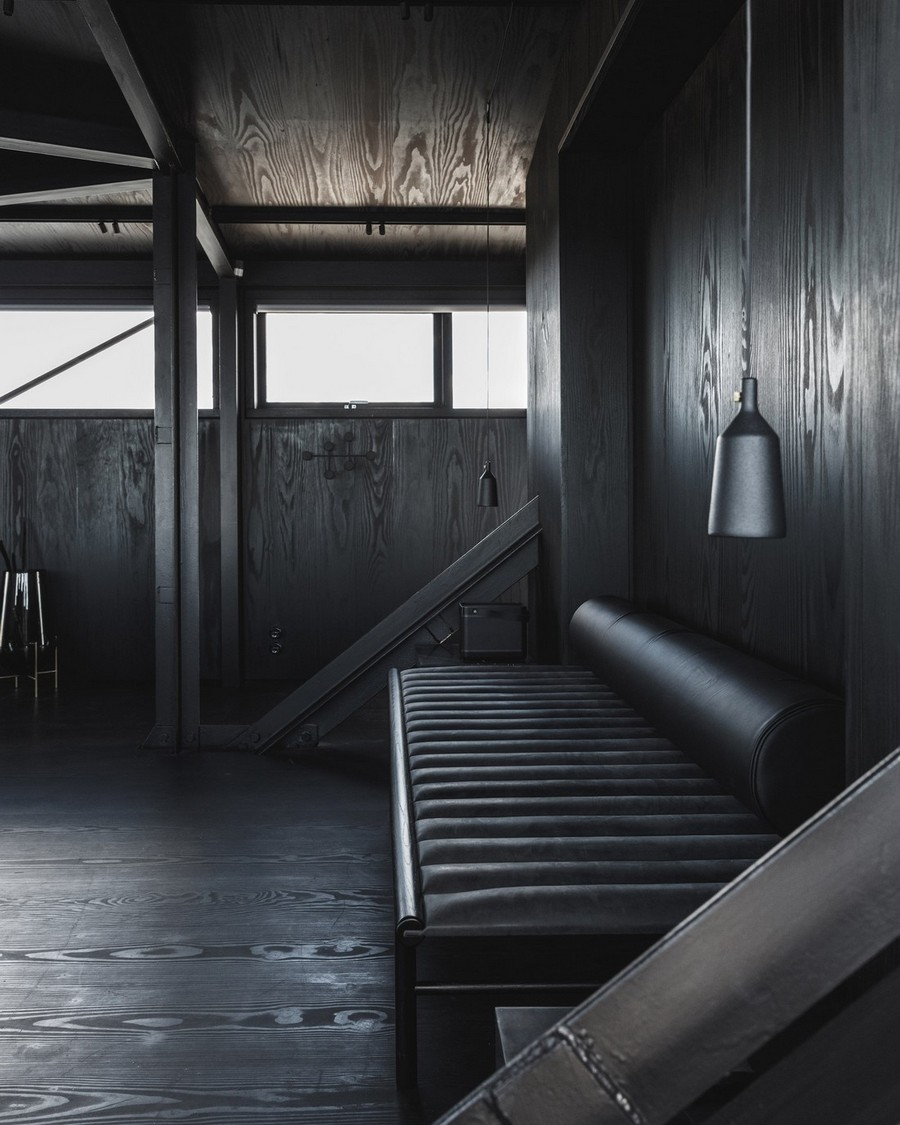 1-5-remade-reconstructed-ex-harbor-crane-apartment-in-Copenhagen-dark-black-graphite-gray-interior-charcoal-wood-walls-leather-couch-pendant-lamp
