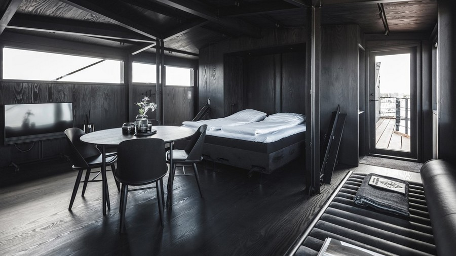 1-9-remade-reconstructed-ex-harbor-crane-apartment-in-Copenhagen-dark-black-graphite-gray-interior-open-plan-bedroom-living-room-dining-area-leather-couch-bed-dining-table-TV-set