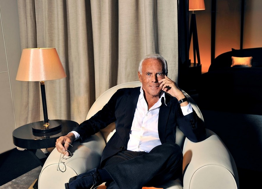 1-Giorgio-Armani-photo-in-interior-arm-chair-with-glasses-black-and-white-suit-beige-curtains-table-lamp