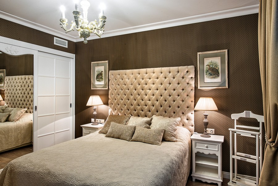 2-neo-classical-style-interior-design-in-beige-brown-and-white-windowless-bedroom-tall-upholstered-capitone-headboard-bed-bird-artworks-nightstands-bedside-lamps-clothes-rack-built-in-closet-mirrored-doors-chandelier