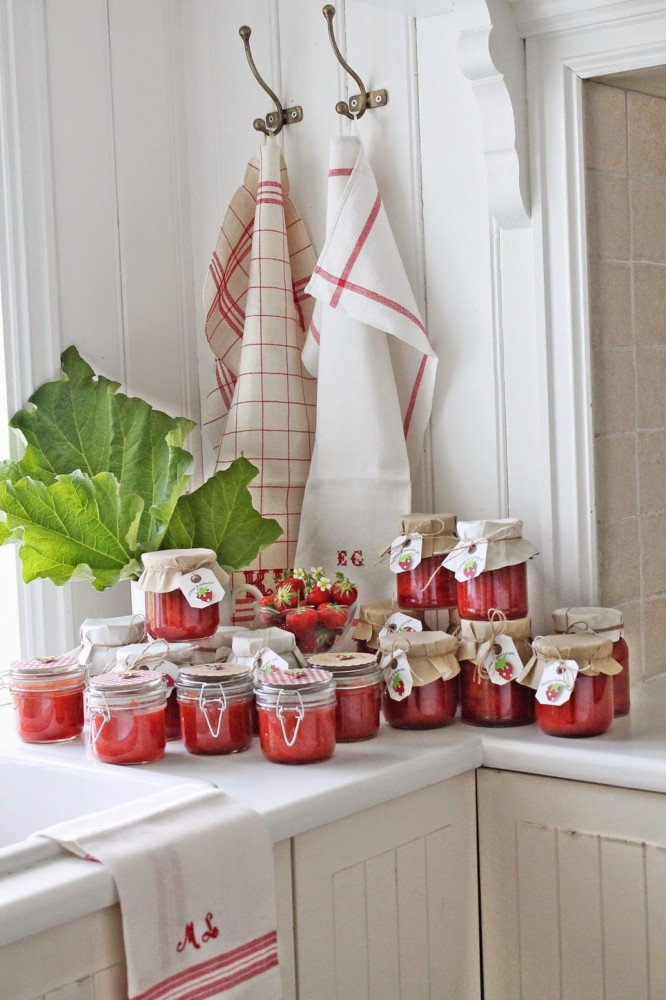 5-red-jars-with-jam-in-white-kitchen-interior-design-towels-racks-strawberries-composition