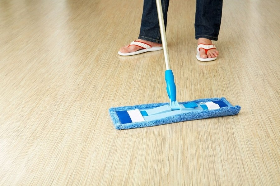 6-woman-cleaning-floor-wiping-with-a-blue-mop