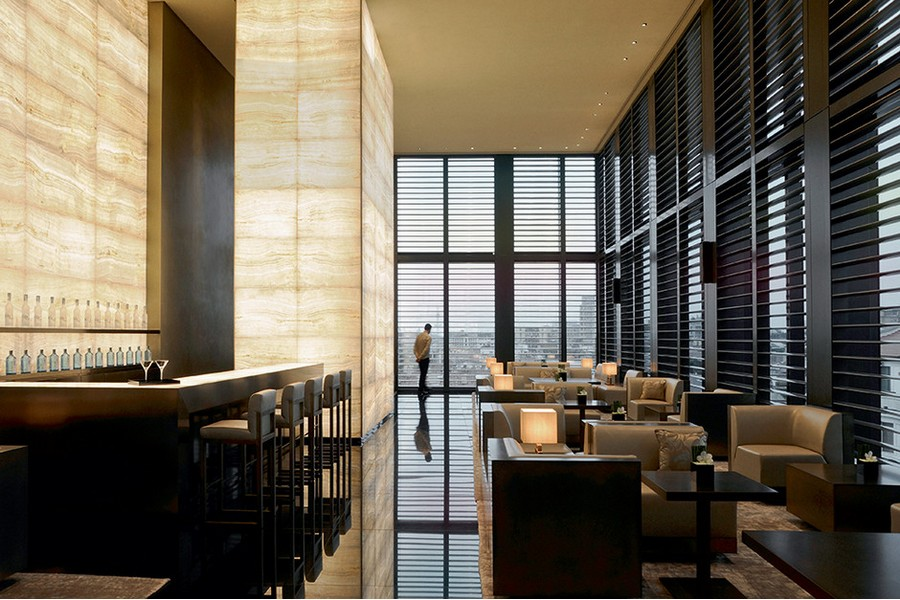 9-1-Giorgio-Armani-Hotel-Milan-luxurious-interior-design-lobby-bar-beige-walls-black-floor-panoramic-windows-venetian-blinds-tables-arm-chairs