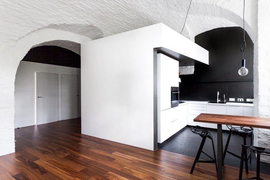 0-minimalist-style-ascetic-interior-painted-white-walls-brick-masonry-arched-ceiling-American-walnut-floor-open-plan-kitchen-set-by-IKEA-bar-table-stools-black-backsplash