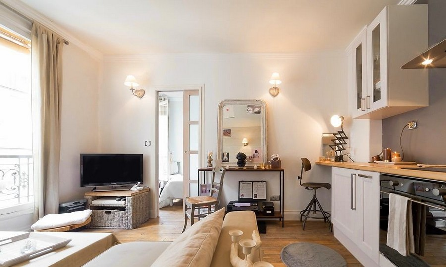 1-2-white-walls-beige-gray-caramel-brown-interior-design-in-French-style-Paris-studio-apartment-kitchen-living-room-boudoir-dressing-table-mirror-cabinets-sofa-TV-set-wicker-basket-sliding-door
