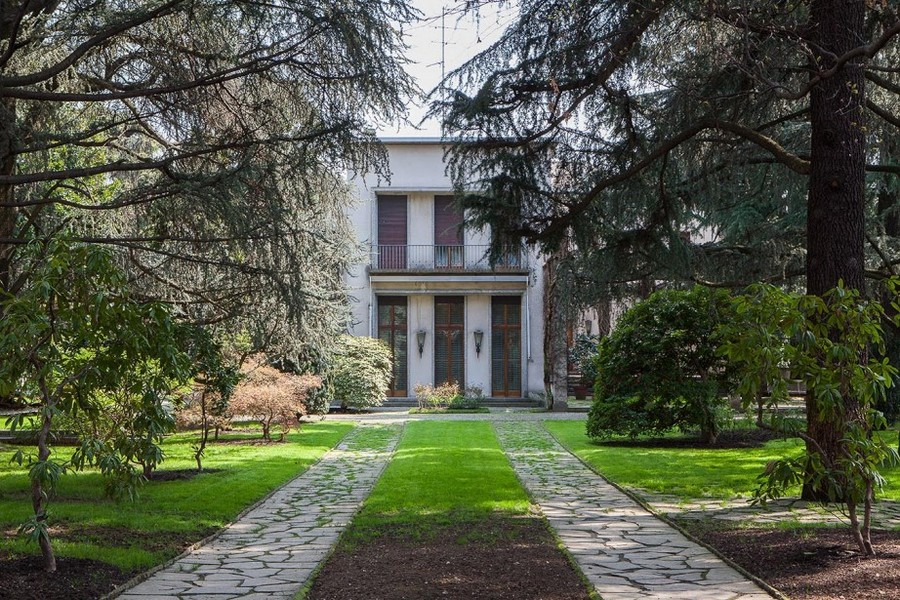 1-Italian-villa-exterior-design-by-Osvaldo-Borsani-big-trees-lawn-stone-path-walkway-coniferous-trees-balcony