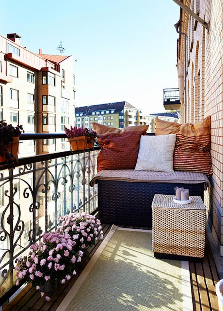 1-cozy-balcony-design-with-a-bench-seat-flowers-rattan-wicker-coffee-table-throw-pillows-forged-wrought-railing