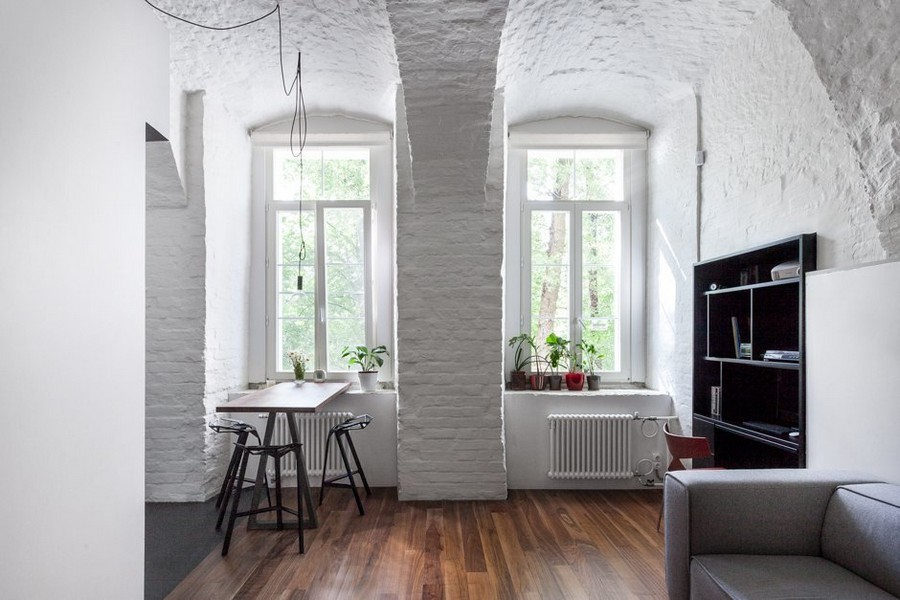 1-minimalist-style-ascetic-interior-painted-white-walls-brick-masonry-arched-ceiling-American-walnut-floor-black-shelving-unit-gray-sofa-bar-stools-table-exposed-wires-bulbs-arched-windows