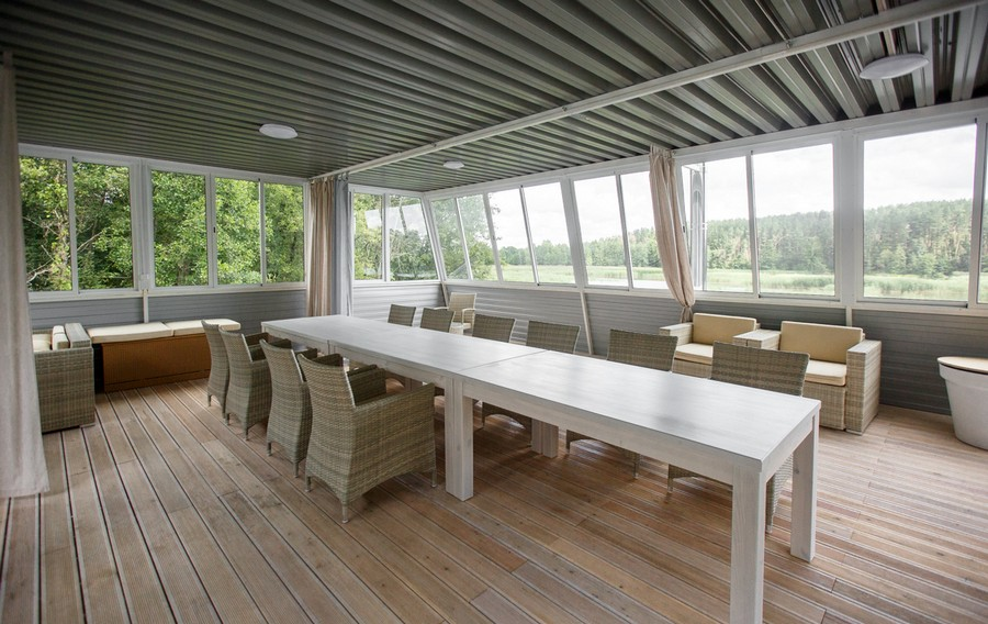 13-houseboat-float-house-interior-design-in-nautical-style-light-larch-wood-floor-light-wooden-furniture-big-dining-room-table-rattan-arm-chairs-big-windows